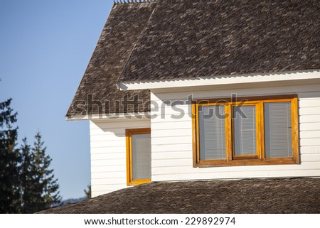 An lateral view at one attic window of a small wooden house in the mountains in autumn. Roof detail can be seen, as well as a clear, blue sky. - stock photo