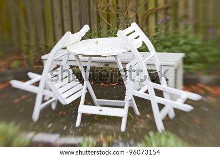 An lens blurred image of garden chairs and table - stock photo