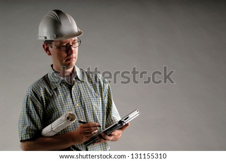 An Male Architect Wearing Glasses Using A PDA Cellphone Isolated On A Grey Background, With Copyspace - stock photo