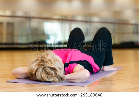 An mature blond woman in a bright pink yoga outfit rests peacefully on her back after exercising in a gym room. - stock photo