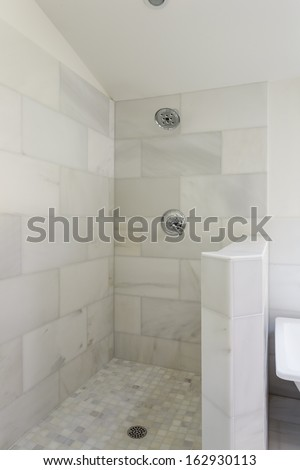 An modern, marble-tiled, open-aired walk-in shower with shower head, fixture, and drain.