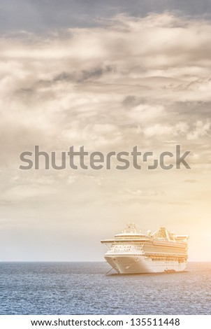 An ocean going luxury liner cruise ship sits on the water at sunset or sunrise. - stock photo
