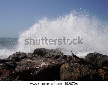An ocean spray on large rocks. - stock photo