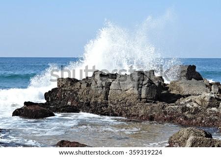 An ocean wave crashes into a rock. - stock photo