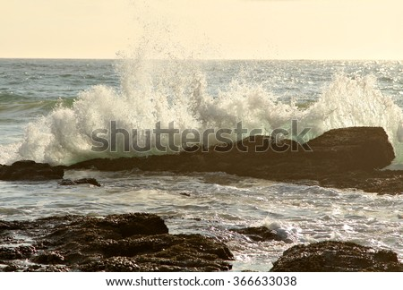 An ocean wave crashes into a rock in the early morning sunlight. - stock photo