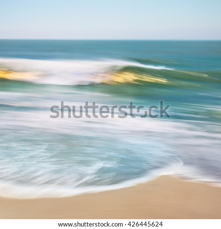 An ocean wave with blurred panning motion and golden sun reflections. - stock photo