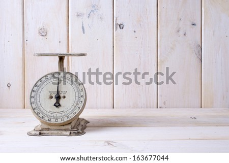 An off white vintage kitchen scale on a white contertop. - stock photo