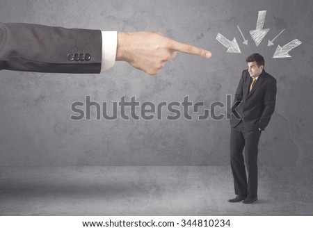 An office boss blaming young amateur and beginner business person with big hand, drawn arrows pointing at him concept - stock photo