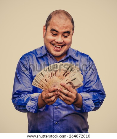 An office guy holding pile of Thai banknotes with his greedy face sweating in grunge vintage atmosphere - stock photo