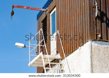 An office or other workplace found at the end of a pier. Steel ladder lead up to closed door. Metal beam with rope at the end, stick out from facade. Picture taken from below. - stock photo