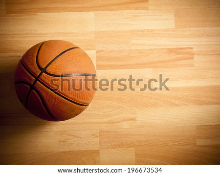 An official orange ball on a hardwood basketball court - stock photo
