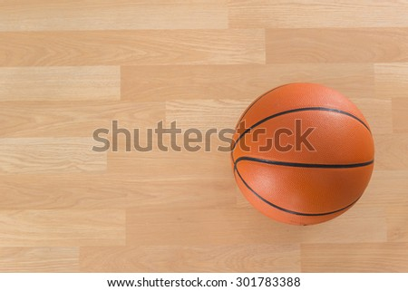 An official orange ball on a hardwood basketball court - stock photo