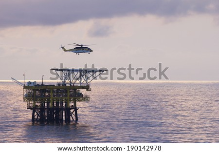 An offshore helicopter transporting roughnecks to oil-rigs - stock photo
