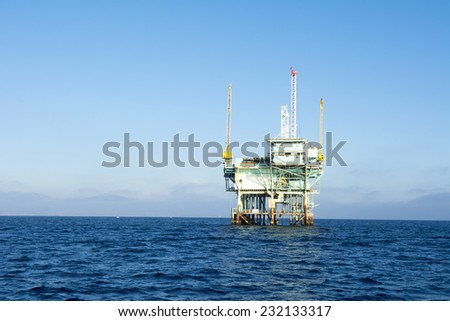 An offshore oil platform rests in deep ocean water on a clear, bright, sunny day.