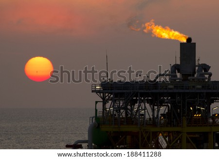 An offshore oil-platform with gas flare during sunset - stock photo