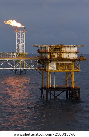 An offshore oil rig at night  - stock photo