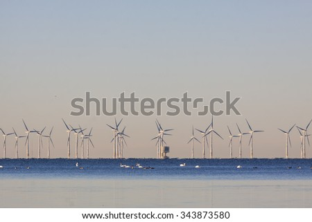 An offshore wind power station in Oresund between Denmark and Sweden when a cold morning in the end of November - stock photo