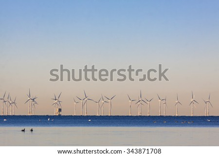 An offshore wind power station in Oresund between Denmark and Sweden when the first cold winter day in the end of November - stock photo