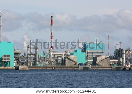 An oil refinery on the coast.  This industrial looking building is located near a port.  There is some gas being released.