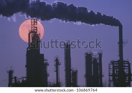 An oil refinery silhouetted against the eerie red of a full moon - stock photo