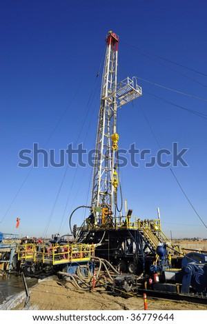 An oil well servicing rig sets up in Kern County California