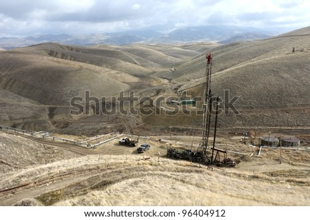 An oil well servicing rig sets up in mountainous country on a California lease - stock photo