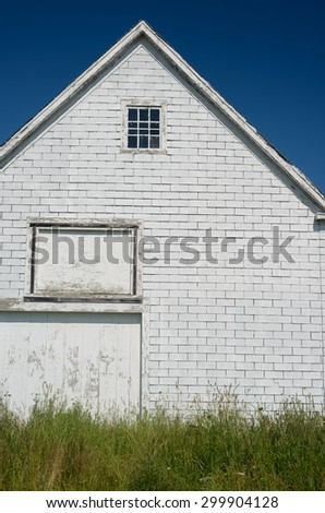 An old a-frame barn sits empty in a field  - stock photo
