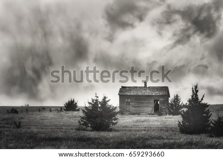 An old abandoned cabin with dramatic clouds.