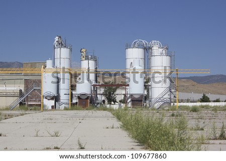 an old abandoned factory with blue skies. - stock photo
