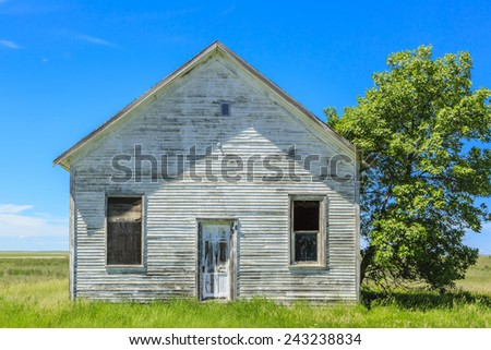 An old abandoned farm house with weathered wood and paint. - stock photo
