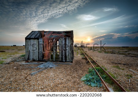 An old abandoned fishing hut on a pebble beach - stock photo