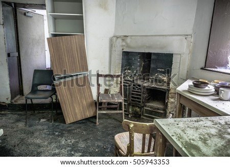An old, abandoned kitchen with old cast iron fireplace.