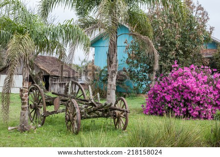 An old abandoned wagon with wooden houses and flowers in the background - stock photo