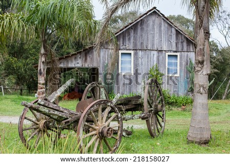An old abandoned wagon with wooden houses in the background