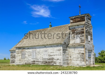 An old abandoned white church with weathered wood and white paint peeling. - stock photo