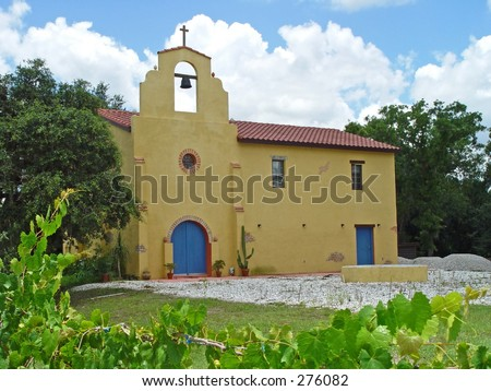 An old adobe, spanish-style mission church with a bell tower, against a blue sky with grape vines in foreground.