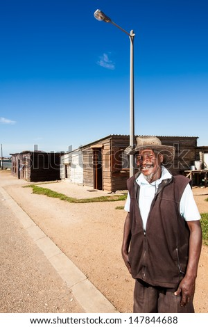 an old african man standing on the curb in the township smiling brightly wearing an old farmers hat - stock photo