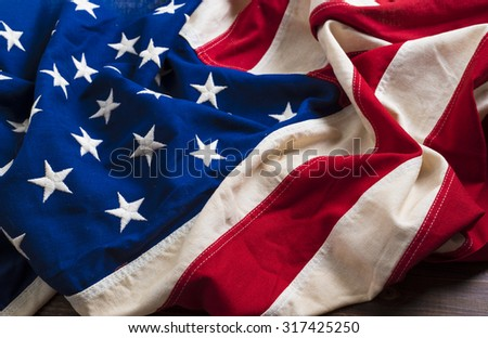 An old american flag on a antique wooden platform with copy space - stock photo