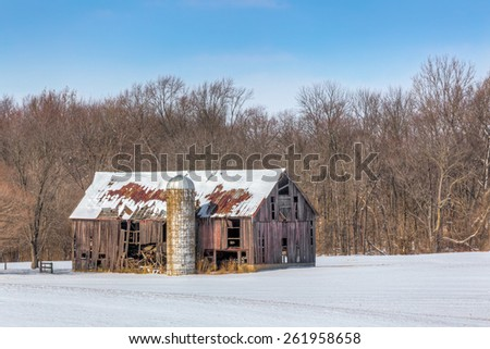 An old and dilapidated barn and silo stand in a snowy landscape on a clear and sunny day.