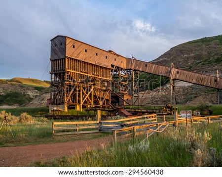 An old and historic coal mine building in the badlands region near Drumheller Alberta Canada at sunset. - stock photo