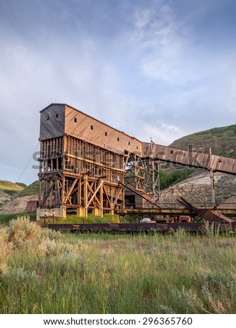 An old and historic coal mine building in the badlands region near Drumheller Alberta Canada at sunset.