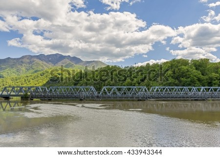 An old and new bridge crossing a big river whit mountains in background
