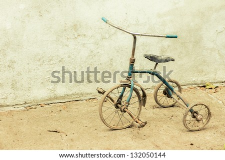 An old and rusty tricycle - stock photo