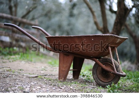 An old and rusty wheelbarrow, in the farm.