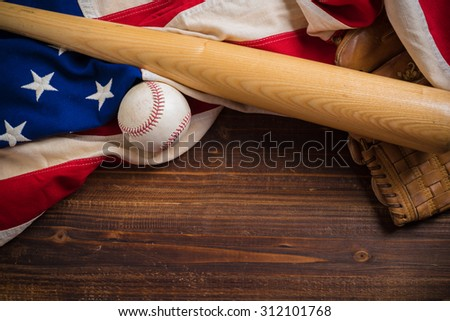 An old, antique American flag with vintage baseball equipment on a wooden bench - stock photo