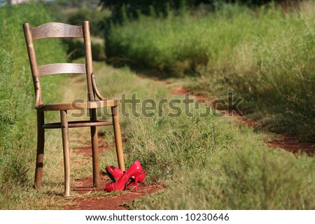 An old antique chair lost in field with red shoes - stock photo