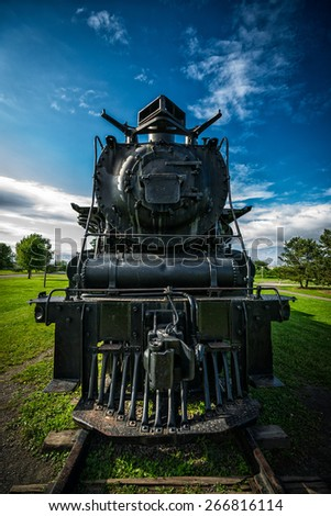 An old, antique diesel powered 4-8-4 Northern style steam train locomotive as seen from directly in front of the engine. - stock photo