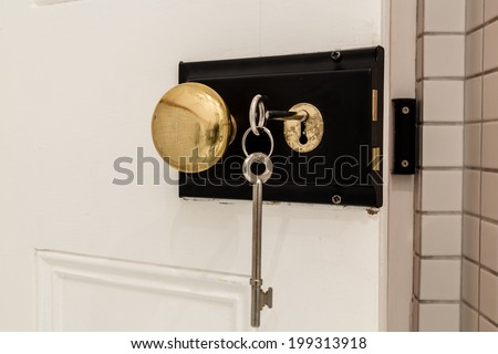 An old antique door lock with long keys and a round knob - stock photo