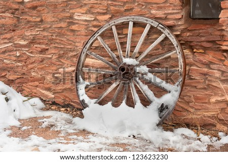 An old, antique wagon wheel covered in snow rests against a ranch facility wall. - stock photo
