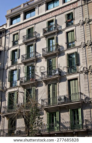 An old apartment block in an urban setting with wrought iron balconies. - stock photo